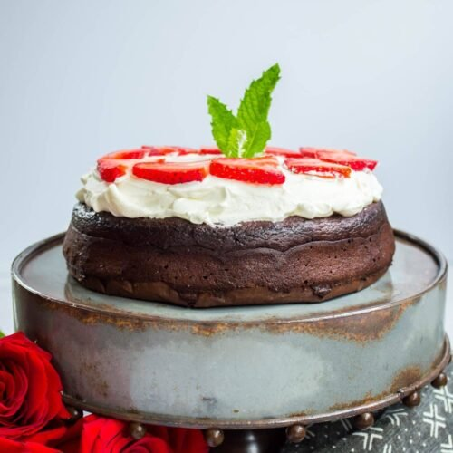 Keto Flourless Chocolate Dessert Torte topped with whipped cream on a cake stand