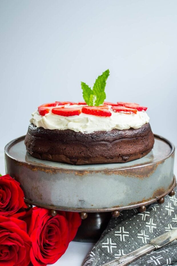 Flourless Keto Chocolate Torte Dessert topped with whipped cream on a cake stand