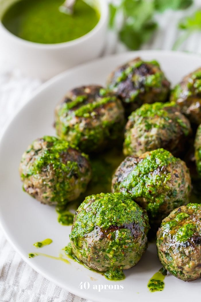 Chimichurri Whole30 meatballs with swiss chard on a white plate
