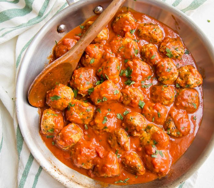 Italian Whole30 meatballs in creamy tomato sauce in a skillet on a dish towel