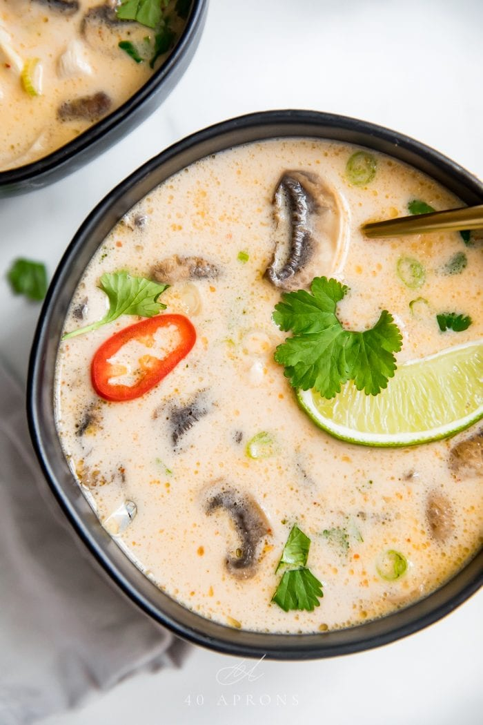 A close up shot of a black bowl of the best tom kha gai Thai chicken coconut soup with limes, lemongrass, chiles, cilantro, and chicken in a coconut broth