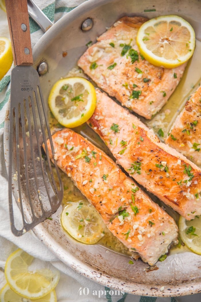 Lemon garlic salmon in a skillet with lemon slices and fish turner