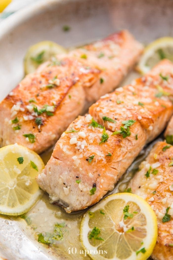 Lemon garlic salmon in a skillet with lemon slices