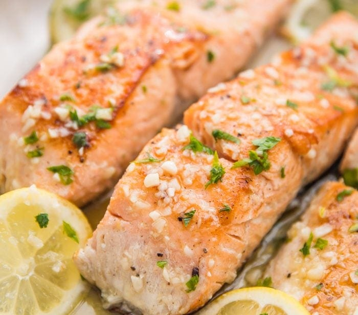 Lemon garlic salmon in a skillet with lemon slices