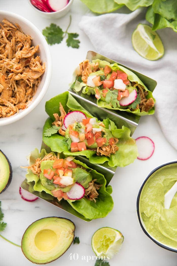 Overhead shot of three paleo chicken tacos in a taco holder served in lettuce wraps topped with avocado crema, pico de gallo, and radishes