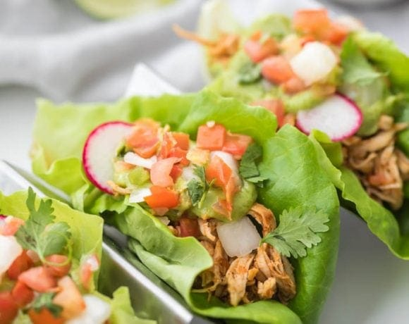 Three paleo chicken tacos in a taco holder served in lettuce wraps topped with avocado crema, pico de gallo, and radishes