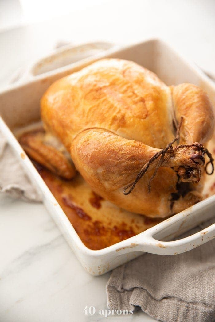 Best easy roast chicken with golden brown skin trussed in a white baking dish