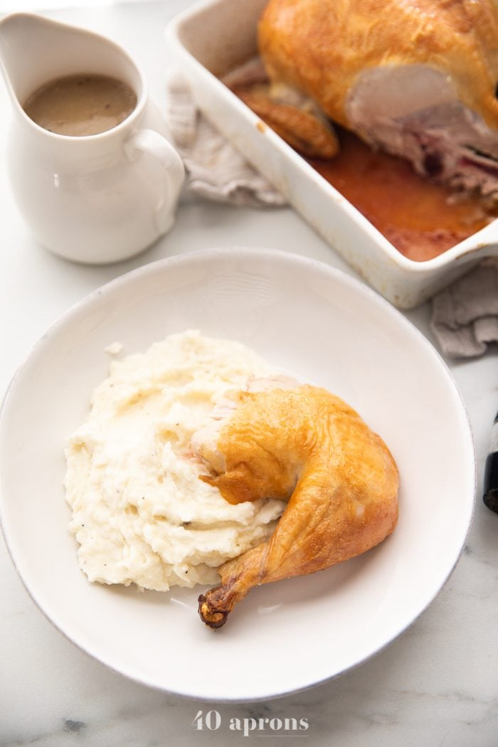 Best easy roast chicken cut into leg and thigh over mashed potatoes