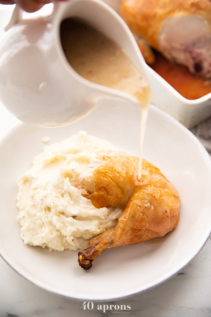 Best easy roast chicken cut into leg and thigh over mashed potatoes with gravy pouring over