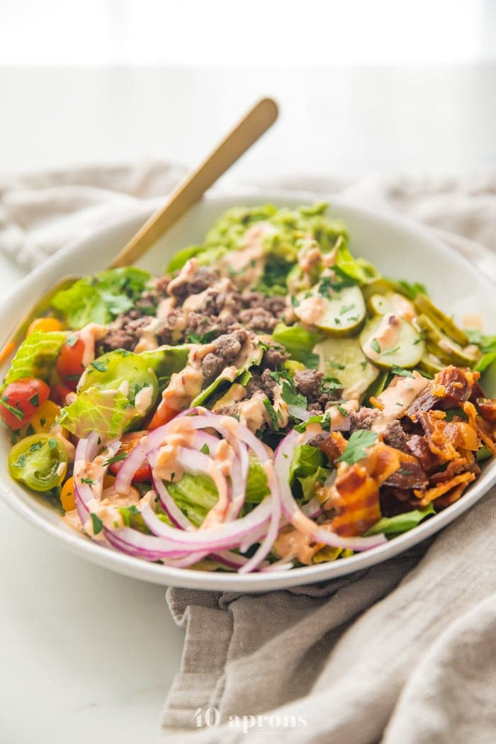 Whole30 loaded burger bowls with ground beef, red onions, bacon, pickles, guacamole, and tomatoes