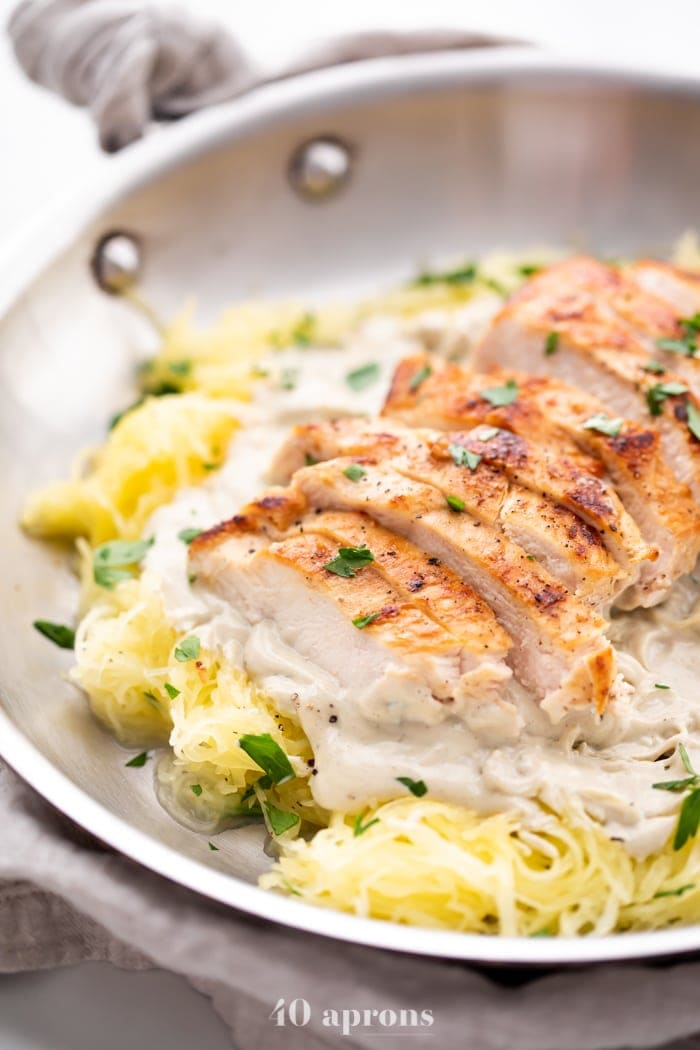 Healthy Whole30 chicken alfredo with spaghetti squash in a skillet topped with parsley