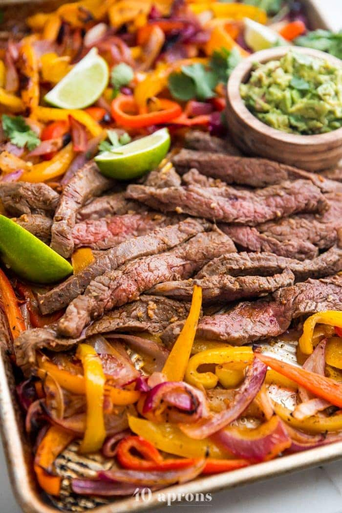 Best sheet pan fajitas with steak and peppers on a sheet pan with lime slices and guacamole off to the side