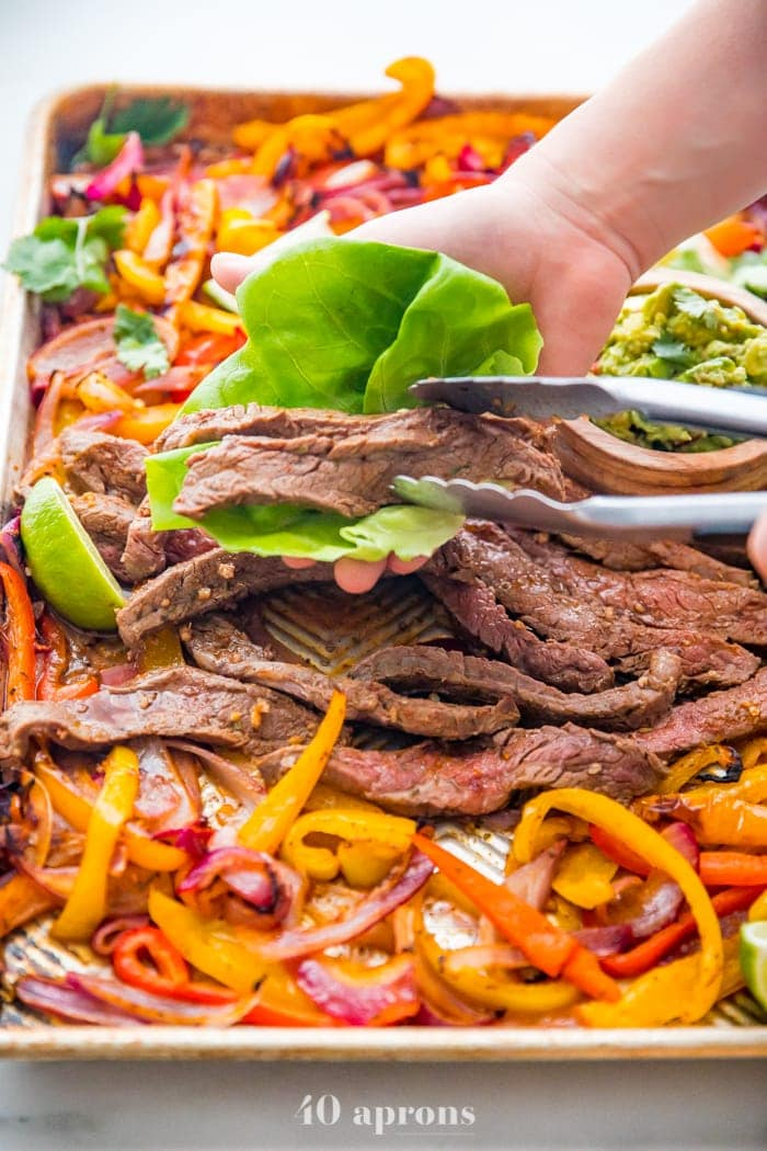 Best sheet pan fajitas with steak and peppers on a sheet pan with a hand putting steak in a lettuce cup