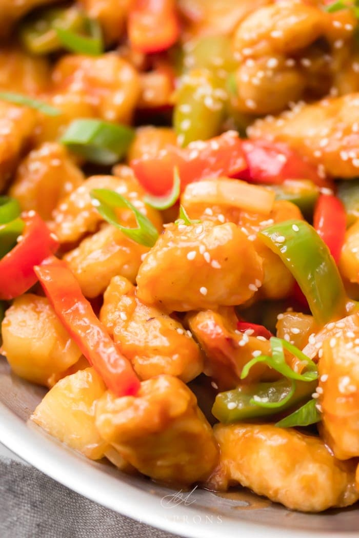 A skillet of healthy sweet and sour chicken with red and green bell peppers
