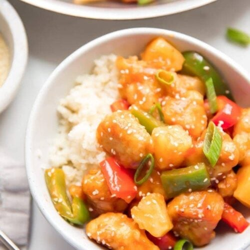 Healthy sweet and sour chicken with peppers over cauliflower rice in a white bowl with sesame seeds and chopsticks to the side