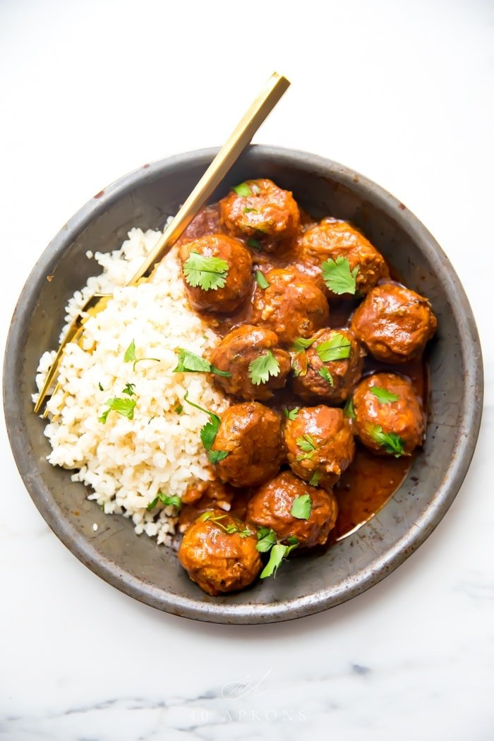Indian meatballs with creamy sauce next to cauliflower rice topped with cilantro in a grey dish
