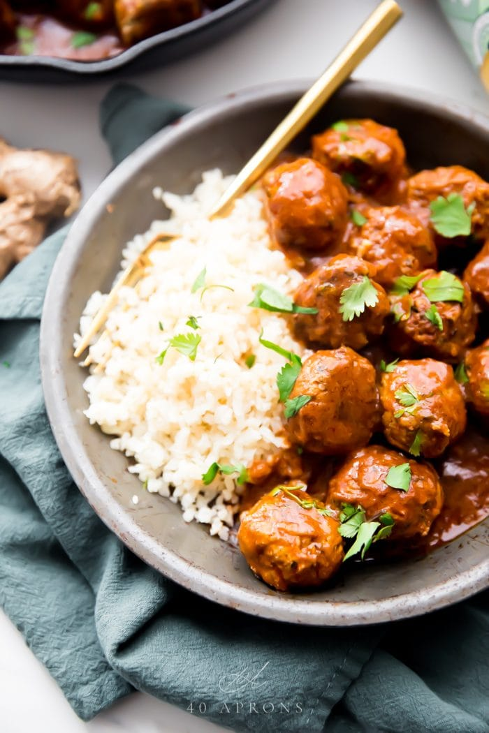 Indian meatballs with creamy sauce next to cauliflower rice topped with cilantro in a grey dish on a green napkin