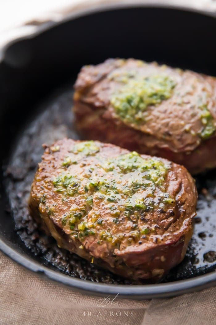 Two of the best ever filet mignon with melted garlic herb compound butter in a cast iron skillet
