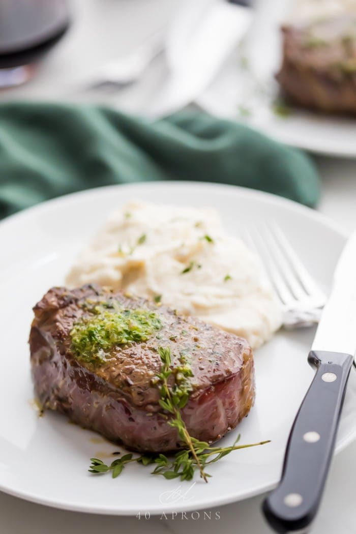 One of the best ever filet mignon steaks with melted compound garlic butter on a white plate with mashed potatoes and fork and knife to the side on a white plate with dark green napkin in the background