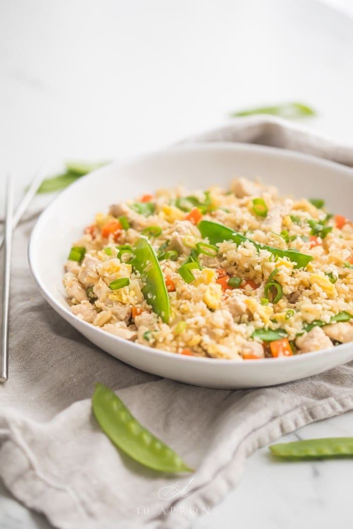 A white bowl of cauliflower fried rice with chicken, peas, carrots with a grey linen and silver chopsticks to the side
