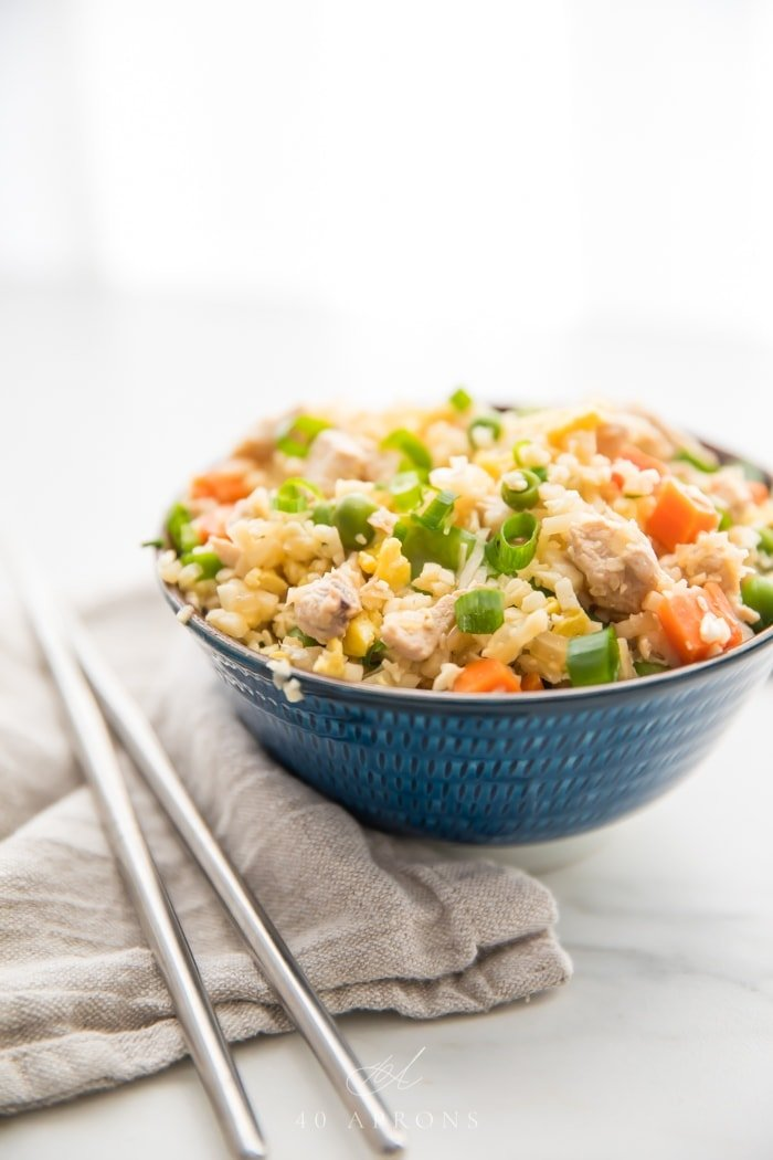 A small blue bowl of cauliflower fried rice with chicken, peas, carrots with a grey linen and silver chopsticks to the side