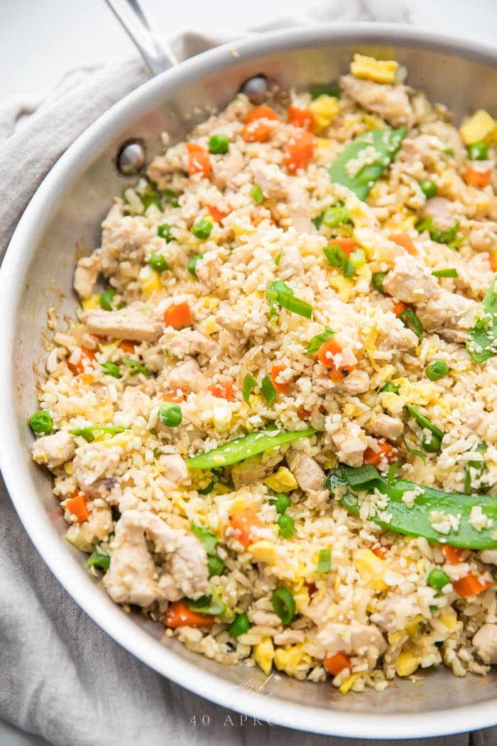 A skillet of cauliflower fried rice with chicken, peas, carrots, snow peas