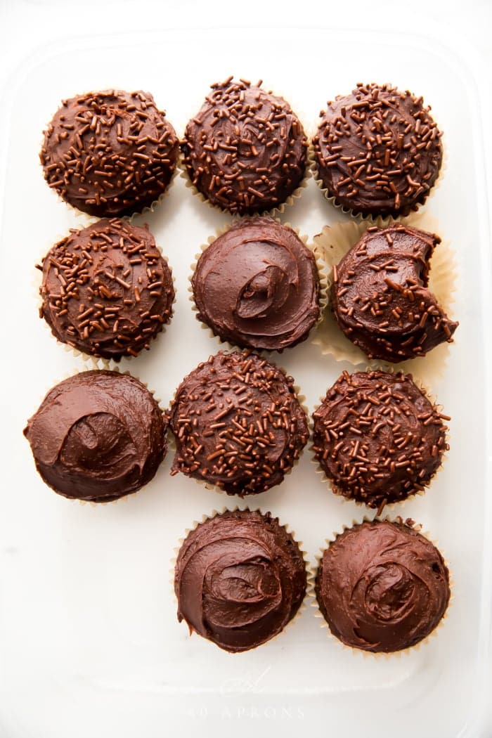 Overhead shot of many chocolate paleo cupcakes frosted with dark chocolate frosting and one bite taken out of one