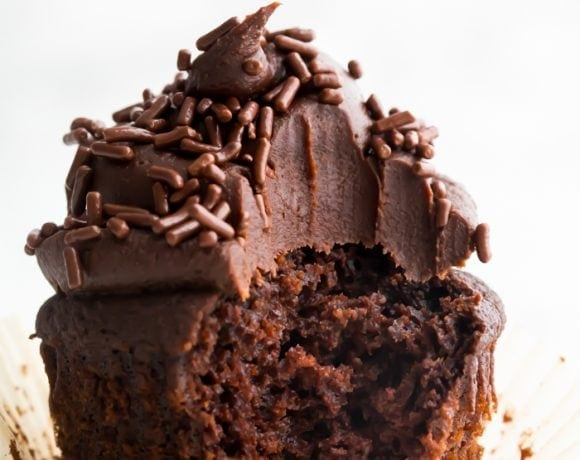 Closeup of chocolate paleo cupcake frosted with dark chocolate frosting with a bite taken out