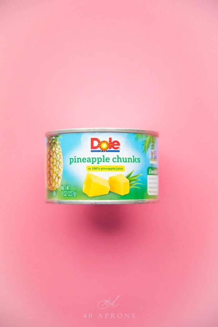Can of Dole pineapple chunks in 100% pineapple juice on a bright pink background