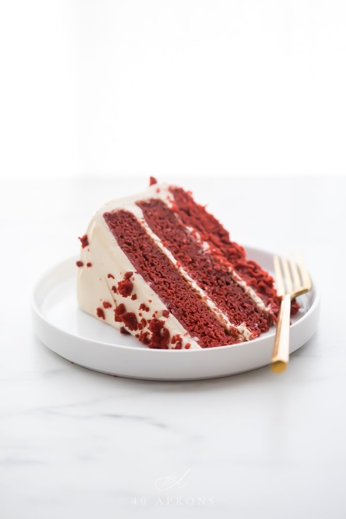 Slice of three layer gluten free red velvet cake with paleo cream cheese frosting on a white plate with a gold fork