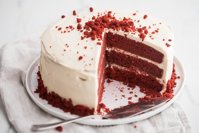 Three layer gluten free red velvet cake with paleo cream cheese frosting sliced open