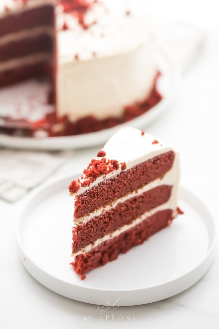 Slice of gluten free red velvet layer cake with paleo cream cheese frosting on a white plate with whole cake in background