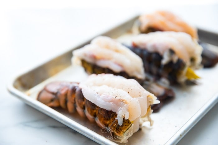 Butterflied lobster tails on a baking sheet