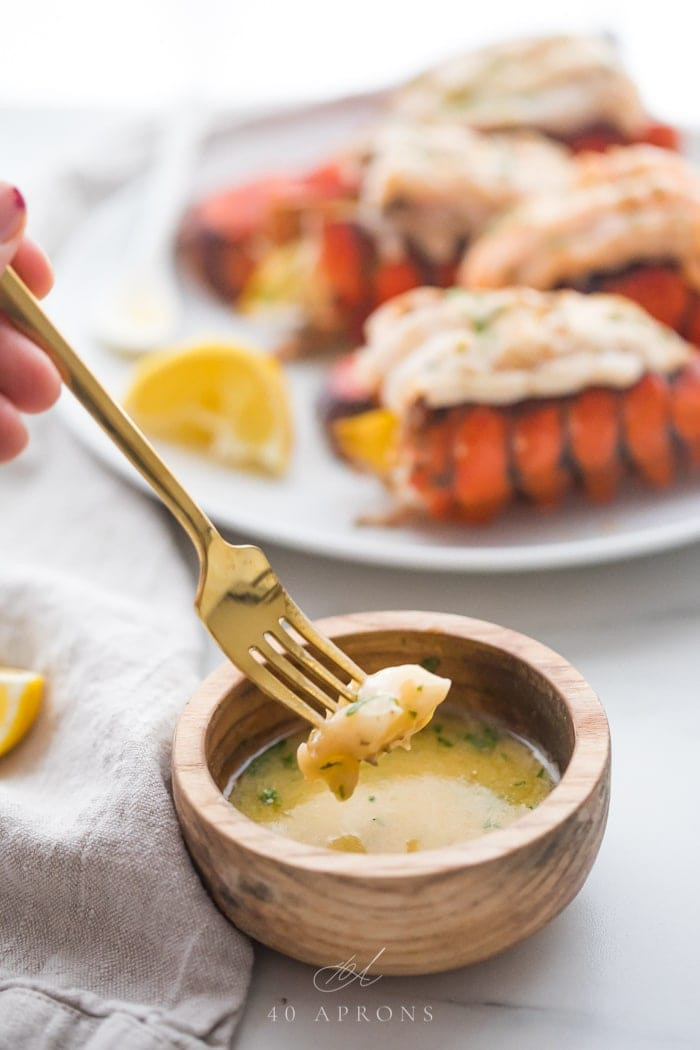 A piece of broiled lobster tail on a fork being dipped into a small wooden bowl of garlic butter dipping sauce with a plate of broiled lobster tails on a plate in the background