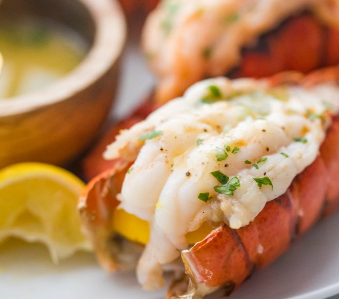 Broiled lobster tails butterflied on a plate with parsley and a lemon wedge next to a wooden bowl of garlic butter dipping sauce
