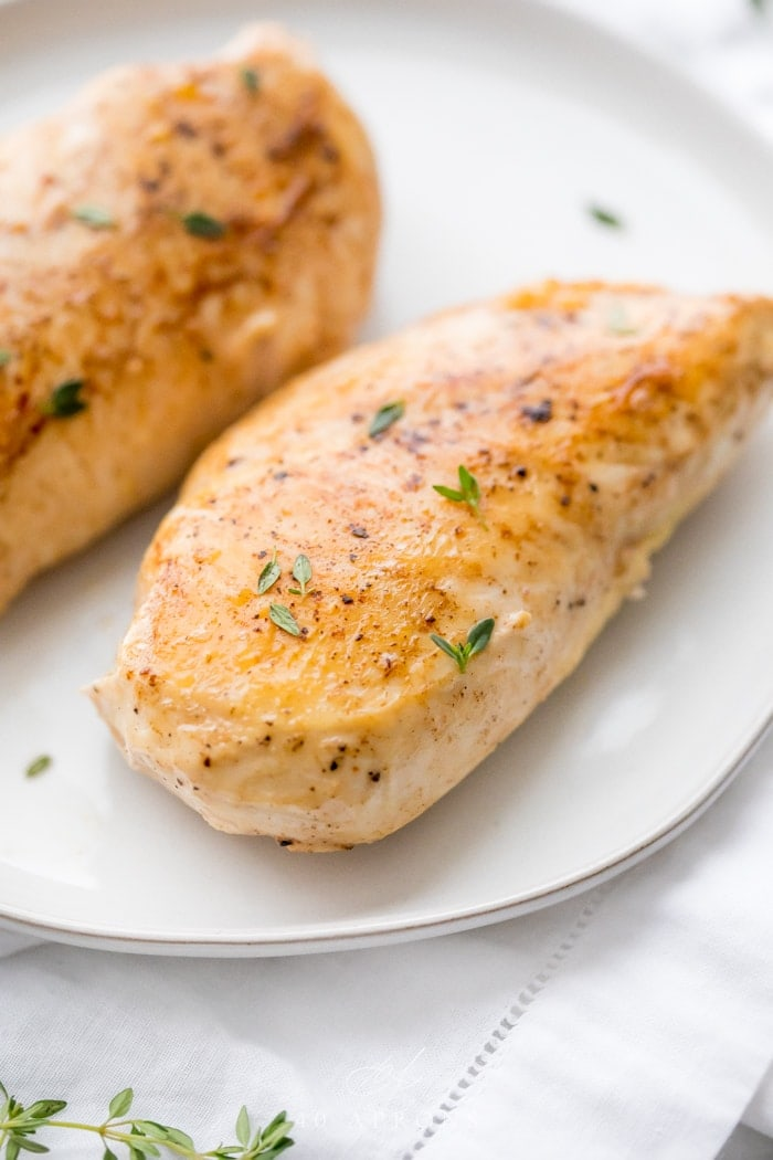 Sous vide boneless skinless chicken breast whole on a plate with thyme garnish