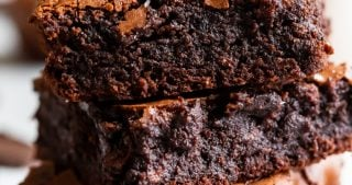 A stack of three paleo brownies showing how fudgy and rich they are, with a crackly top and flake sea salt on top