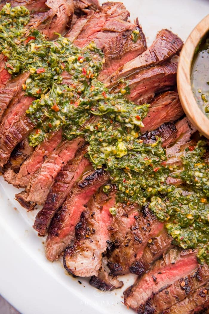 Fresh chimichurri sauce slathered over medium rare silced flank steak