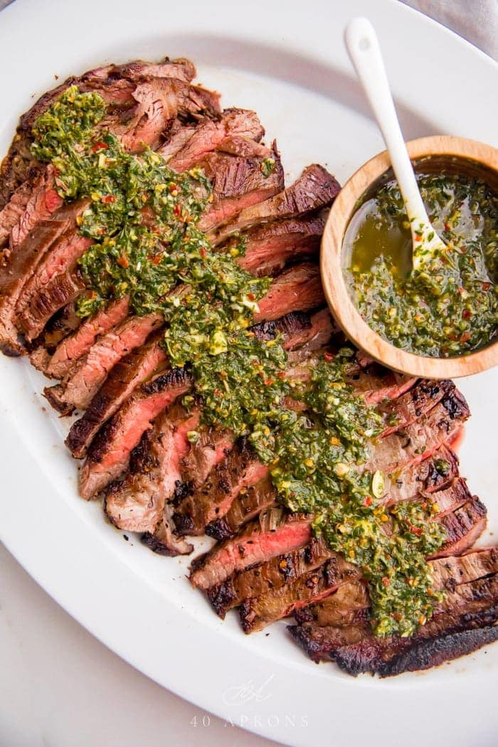 Sliced medium rare flank steak on a plate with lots of fresh chimichurri sauce on top