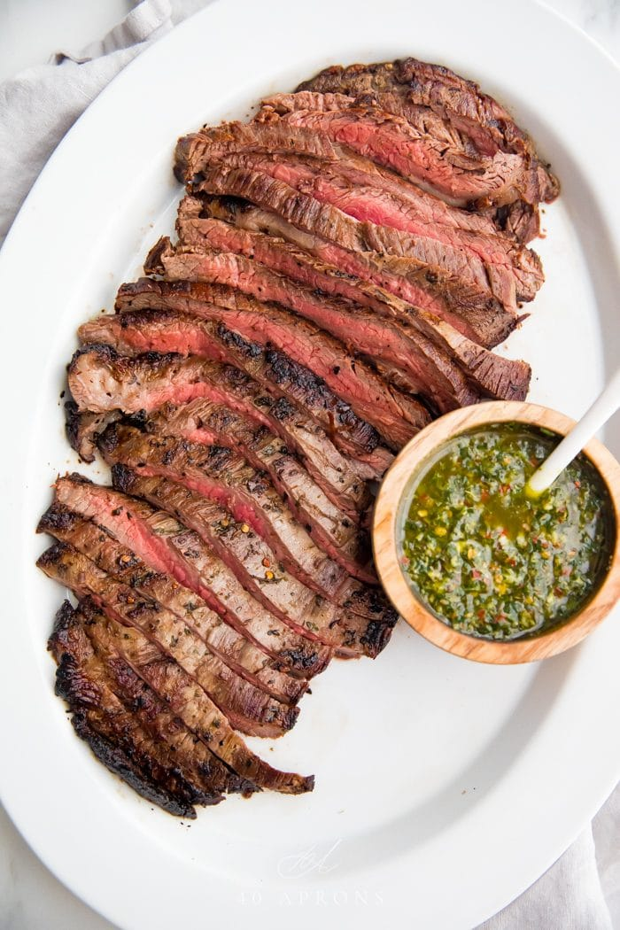A flank steak cut into strips against the grain with a bowl of chimichurri sauce to the side