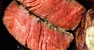 Close up of sliced medium rare filet mignon in a cast-iron skillet