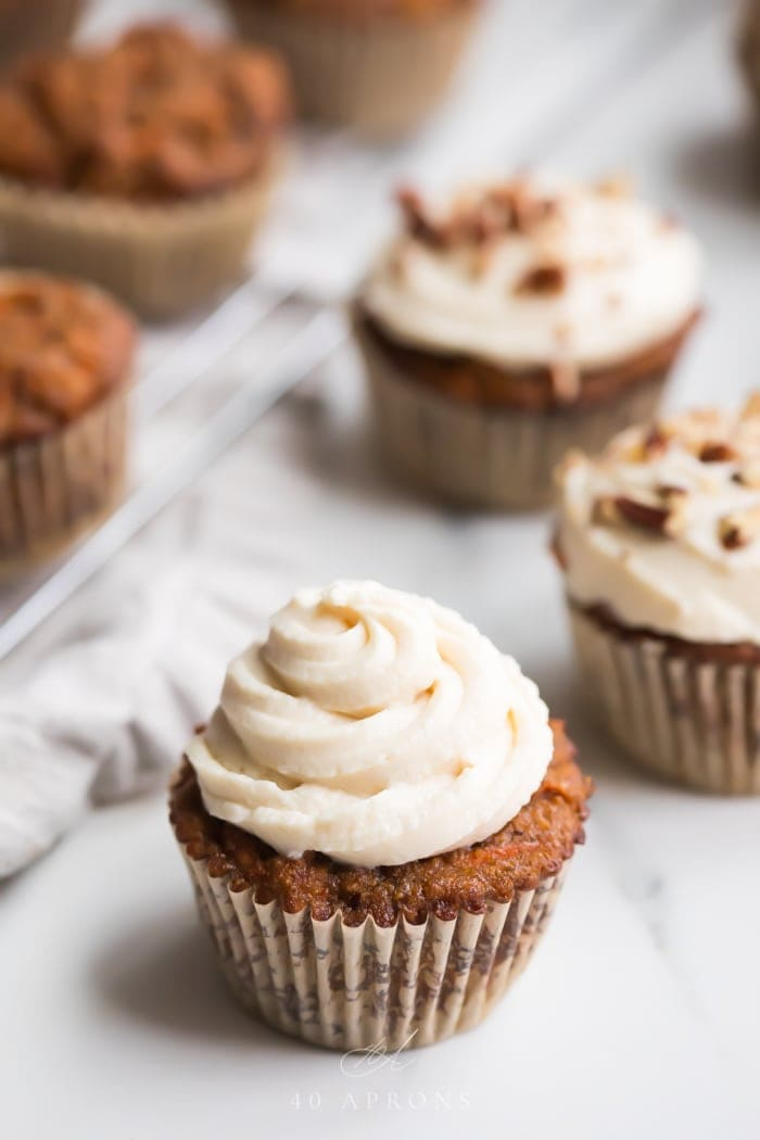 A paleo carrot cake cupcake with a swirl of cream cheese frosting in front of other carrot cake cupakes