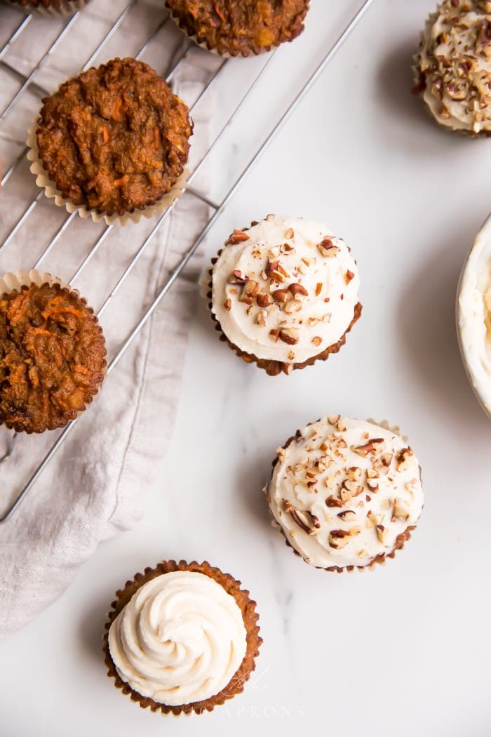 Several paleo carrot cake cupcakes shot overhead with a few frosted with cream cheese frosting and a few naked