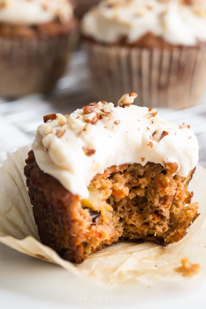 A paleo carrot cake cupcake up close showing the moist interior topped with cream cheese frosting, sprinkled with chopped pecans, with more muffins in the background