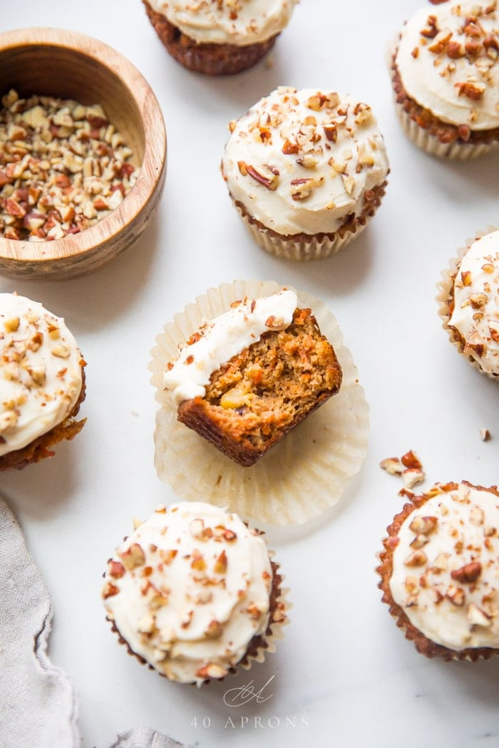 Several paleo carrot cake cupcakes shot overhead with cream cheese frosting and a big bite taken out of one