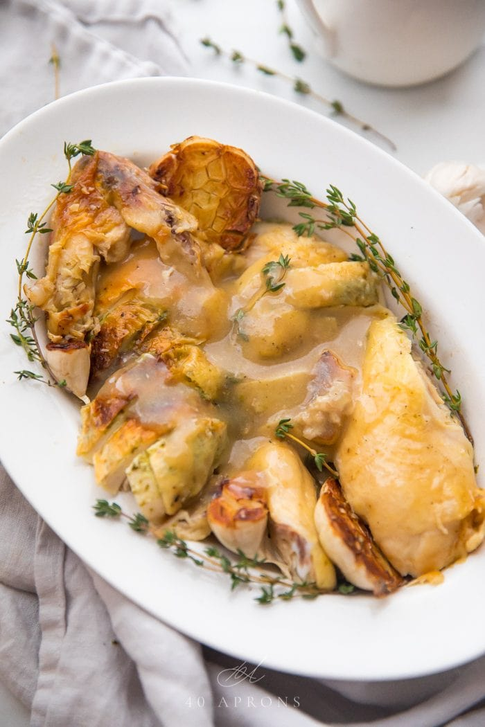 Slow cooker roast chicken cut into pieces topped with gravy and garnished with fresh thyme