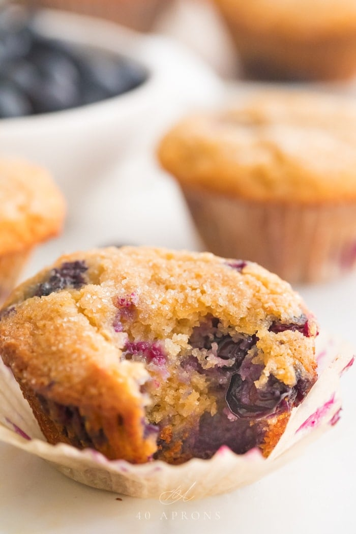 Paleo blueberry muffin with a bite out of it in front of other muffins