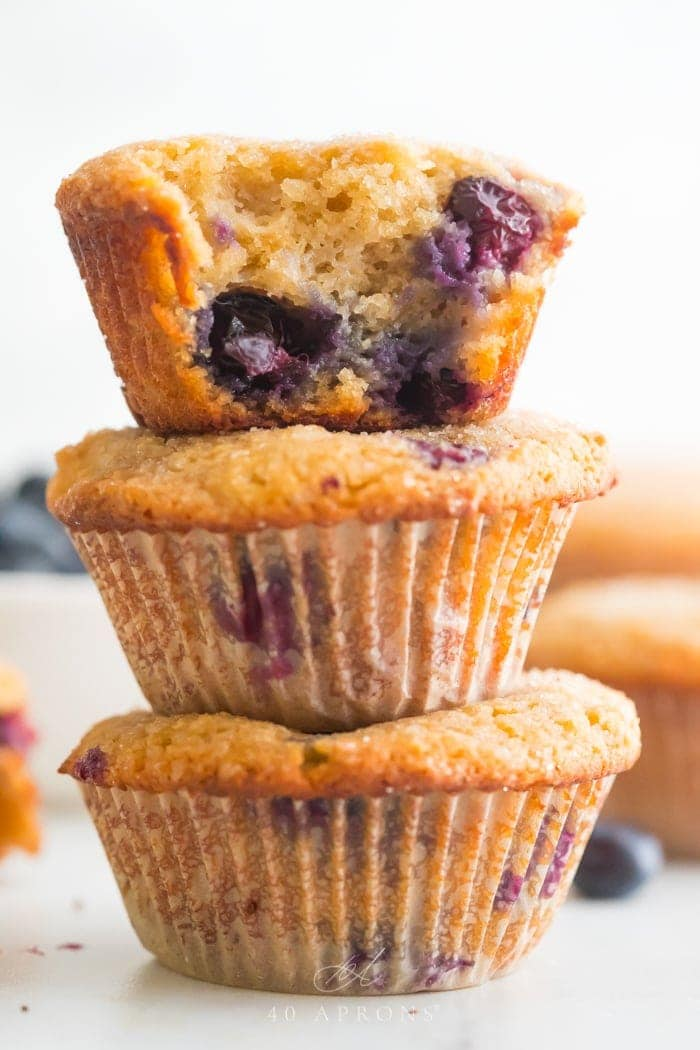 A stack of three paleo blueberry muffins with bite out of one