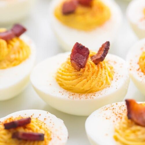 Deviled egg with a couple pieces of bacon on top surrounded by other eggs