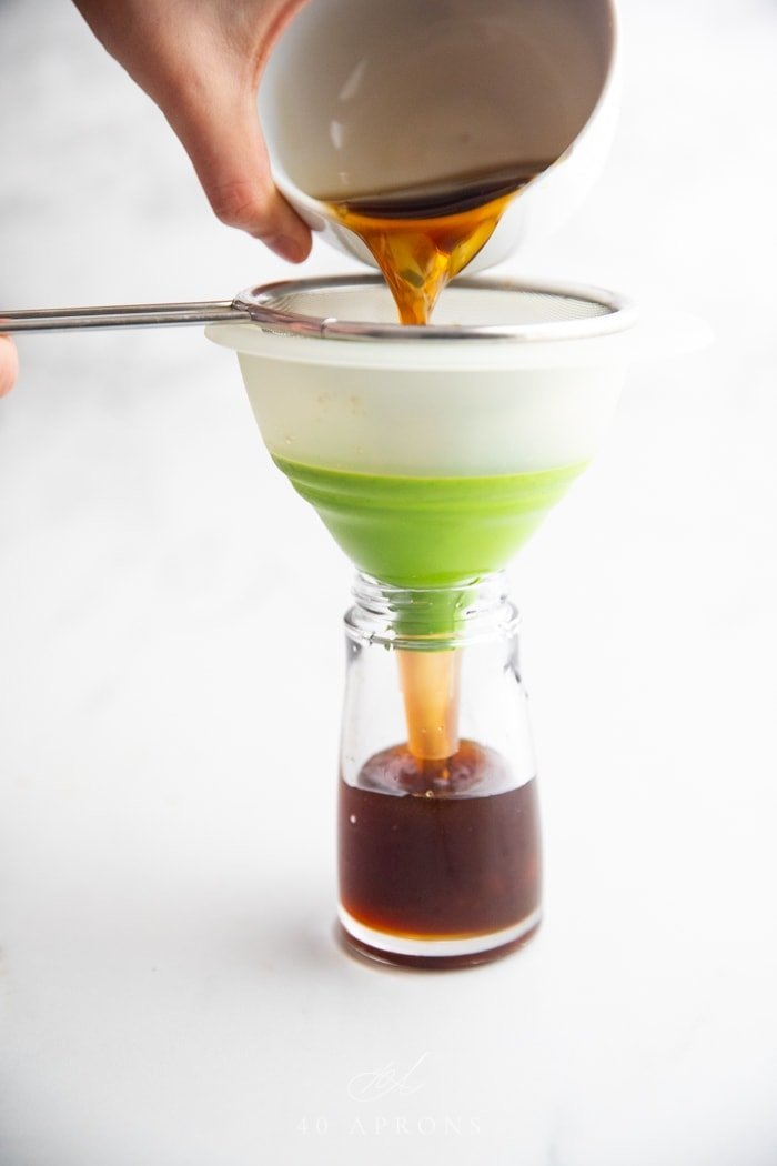 A bowl of soy sauce substitute pouring over a sieve, through a funnel, into a bottle